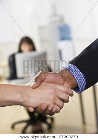 A businessman and woman are shaking hands in an office. There is another woman working on a computer in the background Vertically framed shot.