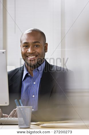 A young businessman is seated at a desk in front of a computer, and is smiling at the camera. Vertically framed shot.