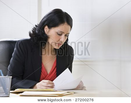 A young, attractive woman is looking over some paperwork on a desk.  She is looking away from the camera.  Horizontally framed shot.