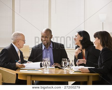 A group of business people are in a meeting in an office.  They are talking and laughing and looking away from the camera.  Horizontally framed shot.