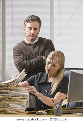 A businessman is standing in an office and looking over a woman's shoulder at the files on her desk.  She is looking away from the camera.