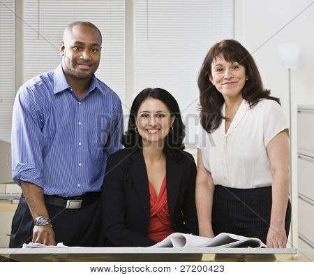 Business team posing for picture, Two white woman and one african american man standing at desk.Horizontal
