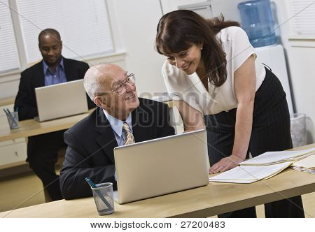 Attractive woman standing over older man helping him with laptop. African American male in back. Horizontal.