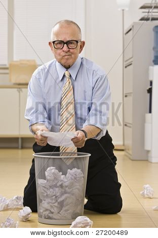 Attractive male senior kneeling on the floor, searching the garbage papers with questioning look, facing the camera. Verical.