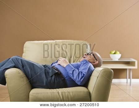 Senior man sleeping on chair with glasses on and hands folded on chest. Horizontal
