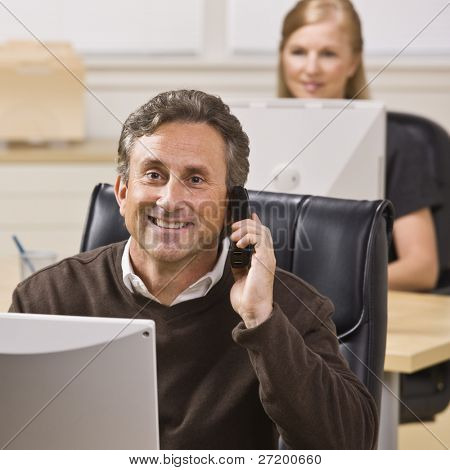 A businessman and woman are working in an office on computers.  They are smiling at the camera. and the man is talking on a cell phone.  Square framed shot.