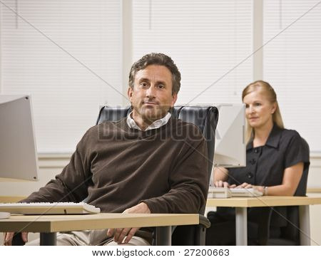 A businessman and woman are working in an office on computers.  The woman is looking at the computer screen and the man is looking at the camera.  Horizontally framed shot.