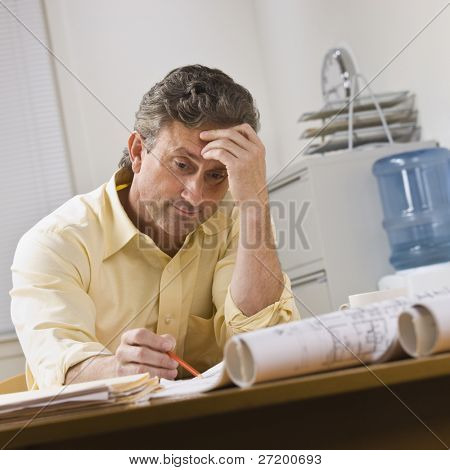 A businessman is working on blueprints in an office.  He is looking away from the camera.  Square framed shot.