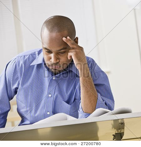 An attractive African-American male studying at a desk. He is resting his head against his fingers, and is puffing his cheeks out with air.  Square composition.