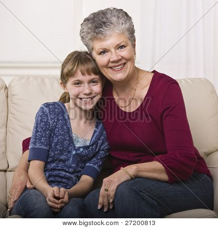 A grandmother is sitting on a couch and hugging her granddaughter.  They are smiling at the camera.  Square framed shot.
