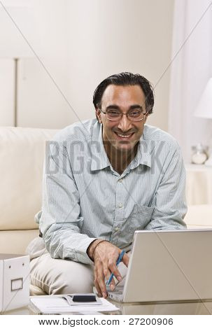 A man is seated in his living room and is working on a laptop.  He is smiling at the camera.  Vertically framed shot.