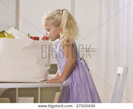 A young girl is peeking into the sack of groceries on the kitchen table.  She is looking away from the camera.  Horizontally framed shot.