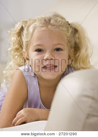 A beautiful little girl lying on a couch and smiling at the camera.  Vertically framed shot.