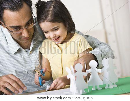 Um pai brincando com sua filha.  Ele é ajudá-la a cortar de bonecas de papel e ela está sorrindo.  Hori