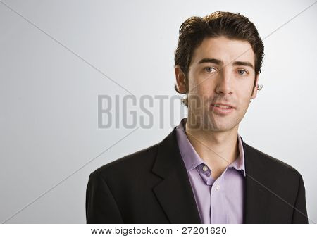 A businssman is standing in a room and looking at the camera.  Horizontally framed shot.