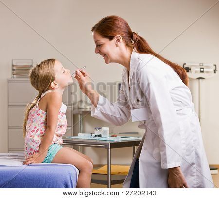 Doctor checking girl temperature