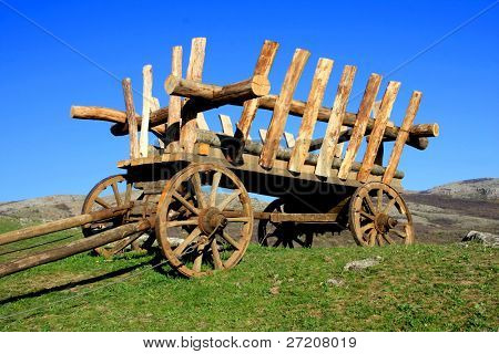 wooden cartage vehicle on green field in mountains