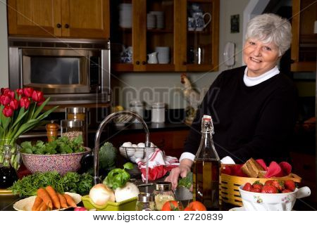 Mature Woman Smiling While Cooking.