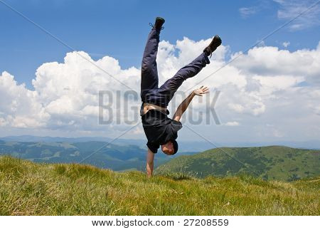 Happy man in mountains stay head over heels on one hand