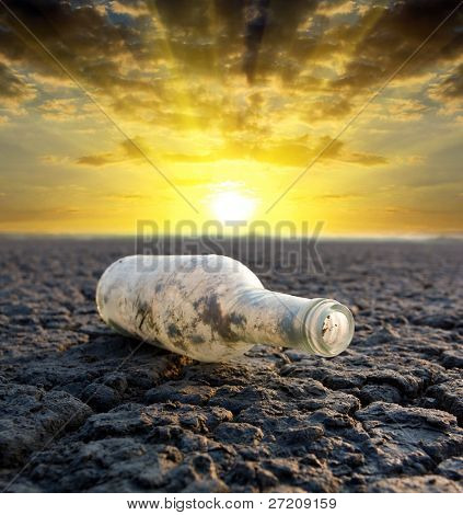 old thrown out bottle on sunset background