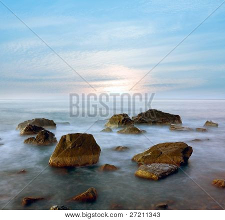 Early morning on sea. Wet stones in water