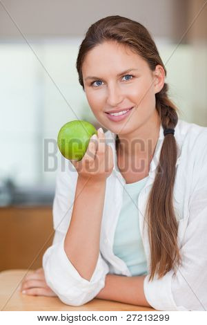 Portrait of a happy woman with an apple in her kitchen