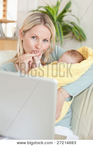Young mother kissing her baby's hand while sitting on the sofa
