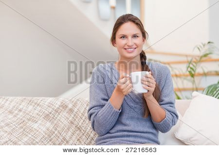Woman holding a cup of tea while looking at the camera