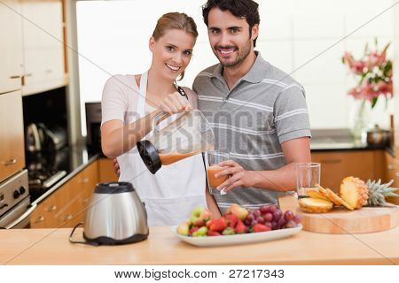 Young couple making fruits juice in their kitchen