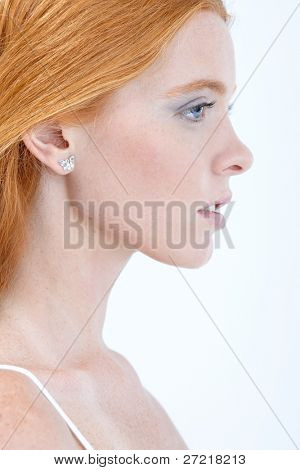 Profile portrait of pure beauty with red hair, side view.?