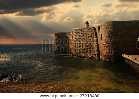 View on Mediterranean sea and ancient walls of Acre at sunset in Israel.