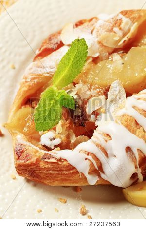 Closeup of danish pastry with apple filling and frosting