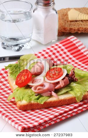 Healthy sandwich with lettuce, canned tuna, cherry tomato and onion circles on a checkered placemat, on a background glass of water, saltcellar and knife