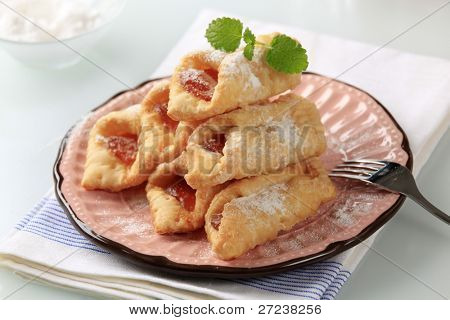 Danish pastry turnovers filled with apricot jam, sprinkled with icing sugar, decorated with mint leafs on a pink plate (horizontal)
