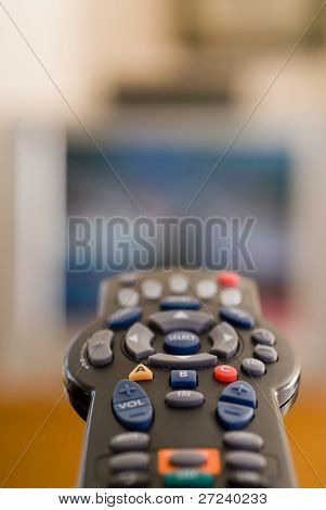 Um controle remoto apontado para a TV mostra o conceito de batata de sofá