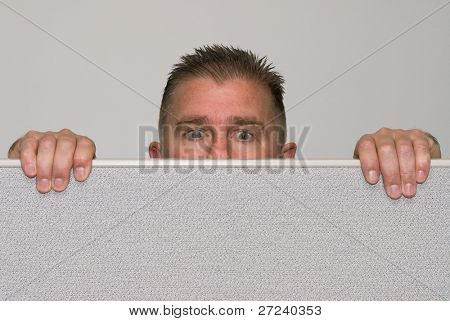 A male office worker peers over a cubicle because he is nosy.