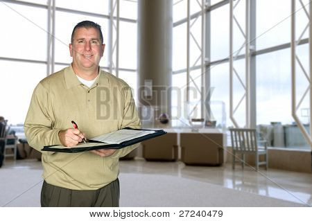 A mature business man wearing casual dress attire taking notes in a large lobby