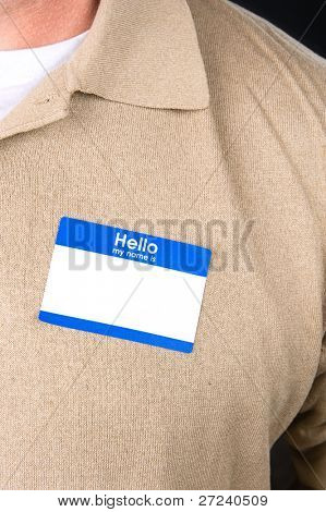 A businessman at a tradeshow wears a blank name tag.