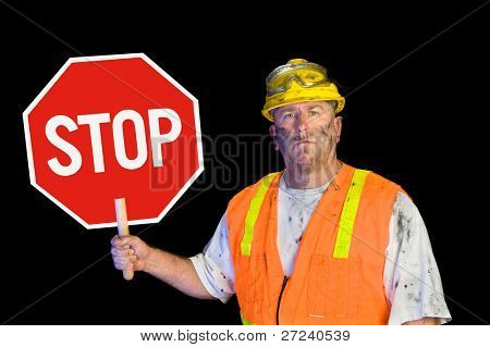 A dirty, grungy, greasy utility construction worker with hard hat, orange vest and eye protection holds up a stop sign.  Isolated on black and can be used as a design element.