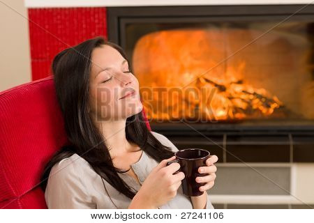 Young woman enjoying winter hot drink relax by home fireplace