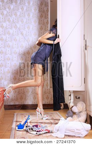 young woman near sliding-door wardrobe with bed linen