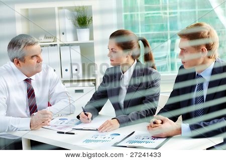 Portrait of busy people discussing new working plan at meeting in office