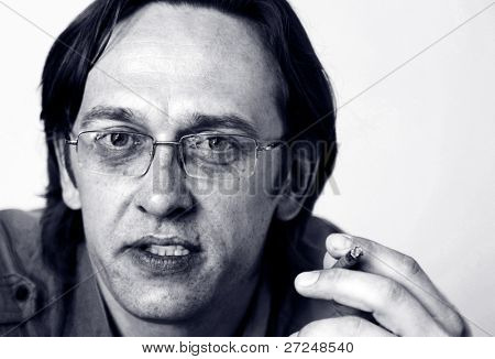 A man wearing glasses smokes a cigarette. Black and white portrait