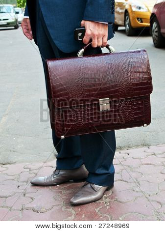 Leather briefcase in the businessman's hand