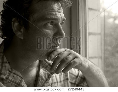 Pensive man looking out the window