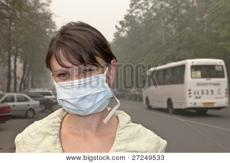 Smog in the city. A woman in medical mask