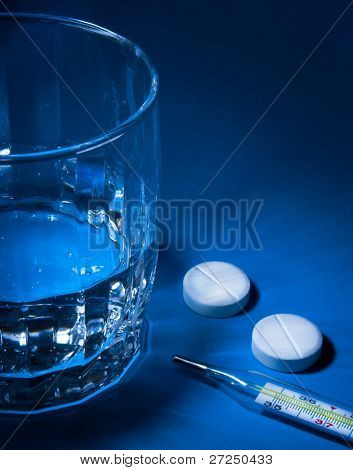 Glass of water, Medical thermometer and two aspirin tablets in a blue light