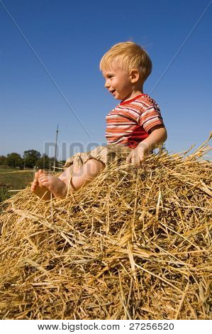 happy barefooted baby boy sit on a hayrick