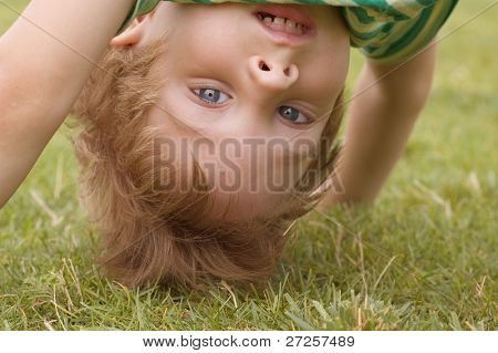 happy little boy stand on head on the summer lawn