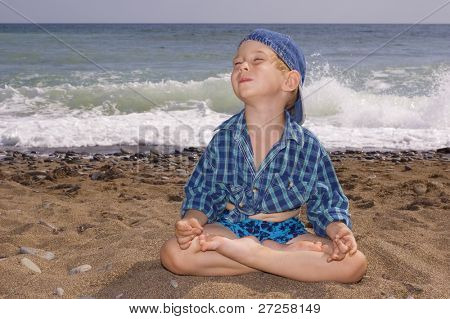 3 years old yogi boy relaxing on the beach